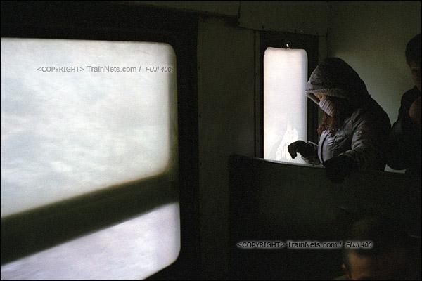 2015年1月。甘肃省白银铁路。下午,接载职工下班的356次通勤车,一位乘客无聊地在朦雾的车窗上画画。(F1004)
