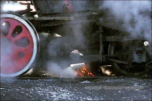 2015年1月。甘肃省白银铁路。位于公司站的机务段,司机正在为机车清炉,还在燃烧炉渣在地上冒着烟。(F1202)