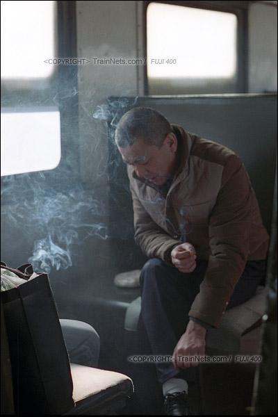 2015年1月。甘肃省白银铁路。下午,355次通勤车,两名进山上班的乘客在抽着闷烟。(F1302)