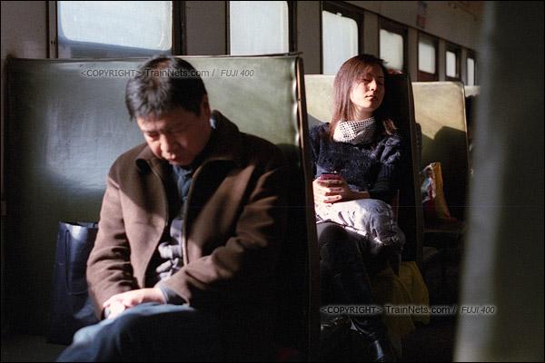 2015年1月。甘肃省白银铁路。下午,355次通勤车,两名进山上班的乘客在打着瞌睡。(F1306)