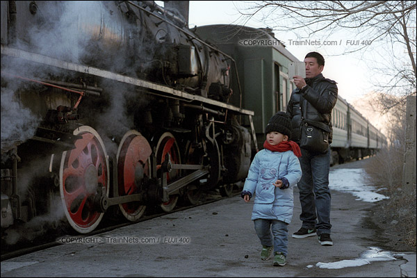 2015年1月。甘肃省白银铁路。列车抵达深部铜矿站,一位父亲带着儿子看蒸汽机车。(F1314)