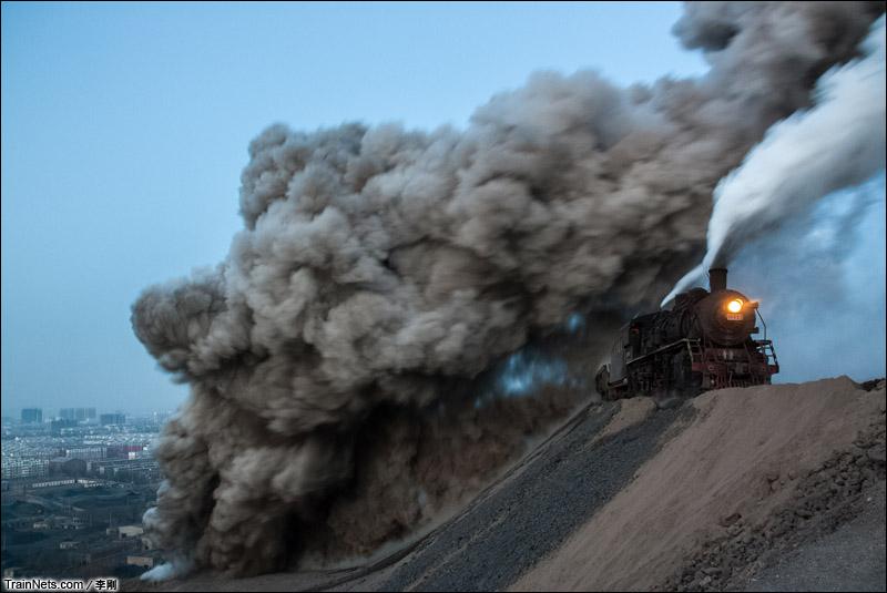 2012年12月15日。辽宁省阜新市。傍晚,上游型蒸汽机车牵引自翻车倾倒炉渣,生成的烟灰漫天飞舞。(图/李刚)