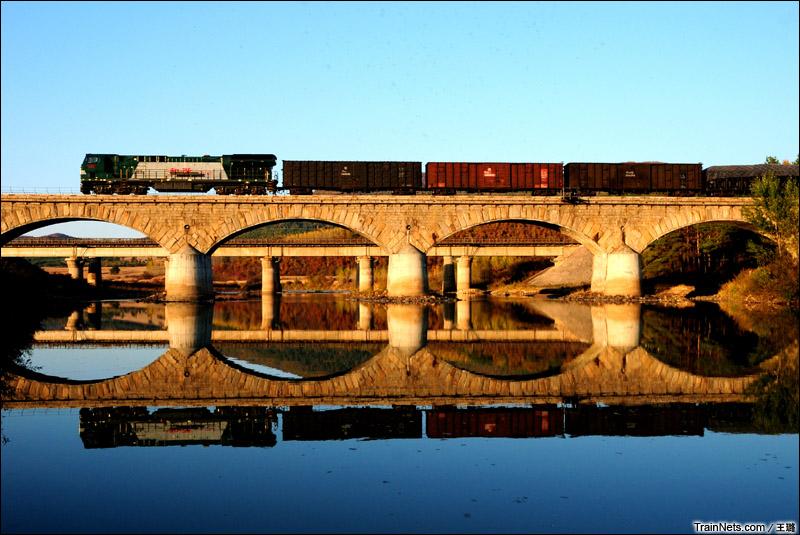 2014年10月。滨绥线。黑龙江省一面坡车站。和谐内5型内燃机车牵引货列通过百年中东铁路石拱桥。