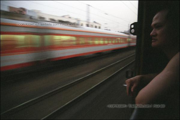 2007年2月,广州。春运期间改用棚车的通勤车在京广线上飞驰,一位乘客站在门边边抽烟边看风景。(A7310)