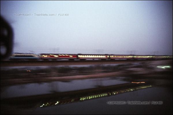 2007年2月,广州。春运期间改用棚车的通勤车在京广线江村货线上飞驰,被不远处一列北行的客车超越。(A7313)