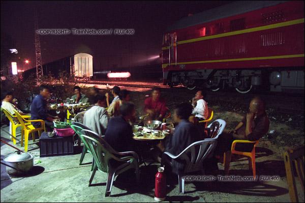 2007年2月,广州。棚车通勤抵达江村编组场后,机车正在调头。路边的大排档生意红火。(A7317)