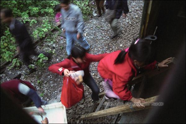 2007年2月,广州。傍晚,不少沿线的居民搭乘开往广州江高镇的棚车通勤列车,由于货车没有梯子,乘客必须通过木梯上下车。(A7330)