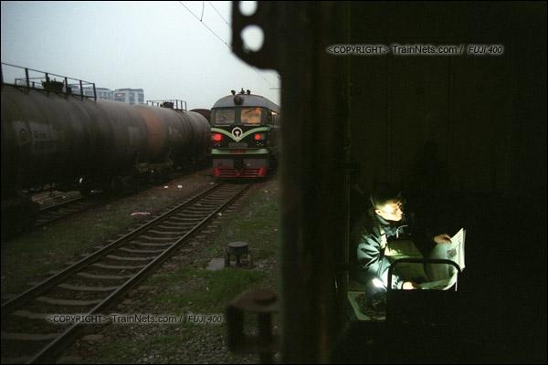 2007年2月,广州。傍晚,春运期间改用棚车的通勤车在京广线上会车。一位乘客借着乘务员手电筒发出的光看报纸。(A7331)