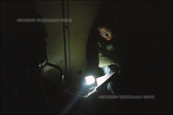2007年2月,广州。傍晚,春运期间改用棚车的通勤车在京广线上会车。一位乘客借着乘务员手电筒发出的光看报纸。(A7334)