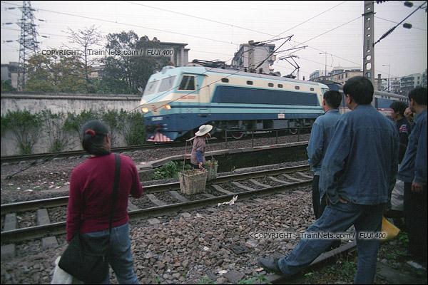 2007年2月,广州。清晨,不少乘客在京广线旁等待开往广州江高镇的棚车通勤车。(A7407)