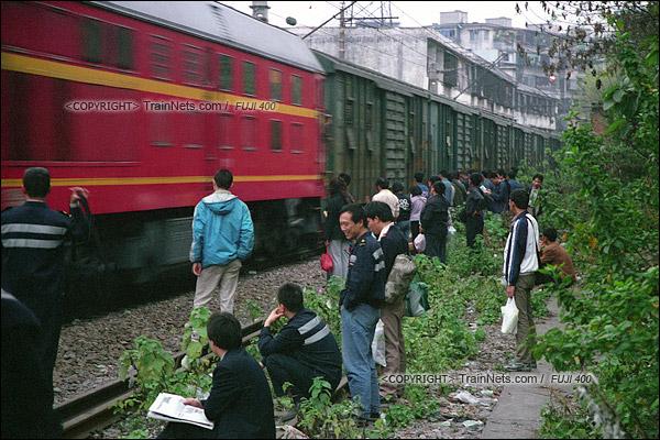2007年2月,广州。清晨,春运期间改用棚车的通勤车抵达,不少乘客站在京广线旁等待上车。(A7414)