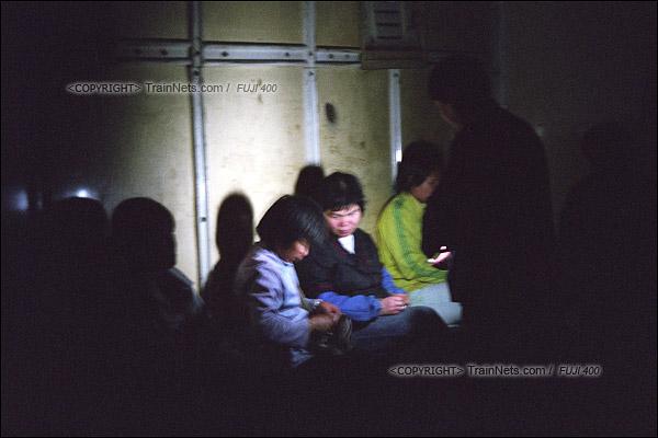 2007年2月,广州。清晨,不少沿线的居民搭乘开往广州江高镇的棚车通勤列车,乘务员拿着手电筒向乘客买票。(A7419)