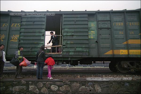 2007年2月,广州江高镇。清晨,开往广州的棚车通勤列车进站。乘务员准备放下上下车用的木梯子。(A7428)