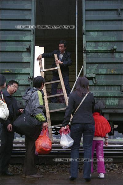 2007年2月,广州江高镇。清晨,开往广州的棚车通勤列车进站。乘务员准备放下上下车用的木梯子。(A7431)