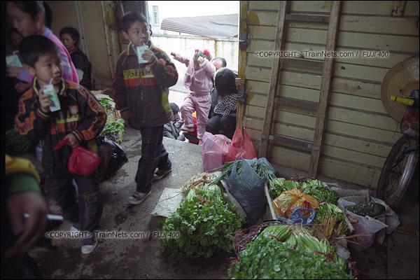 2007年2月,广州江高镇。清晨,开往广州的棚车通勤列车停站,不少沿线的居民上车,车里已经堆满了运去广州出售的蔬菜。(A7513)