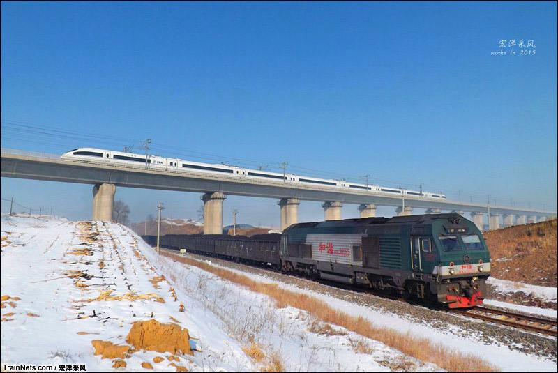 2015年1月22日。辽宁省铁岭市。镇西堡镇木厂村,哈大高铁与铁法线两车交汇。