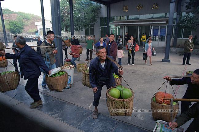 2013年10月。渝怀线。锦和站,不少菜农看到火车进站,连忙抬起沉重的扁担准备上车。(E1431)