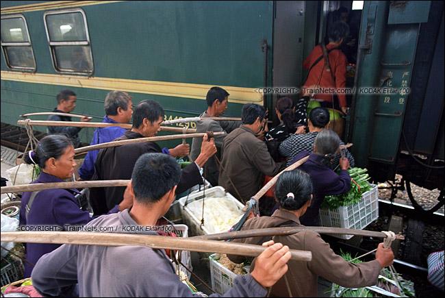 2013年10月。渝怀线。锦和站,菜农挑着担子挤在车门前。(E1434)
