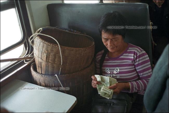 2013年10月。渝怀线。前往怀化的7271次列车,一位菜农在车上数着今天赚的钱。(E1735)