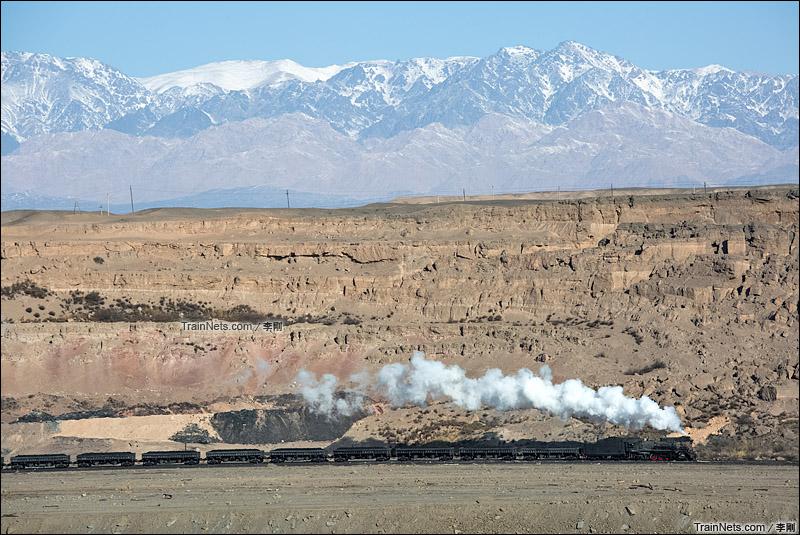 2015年2月22日。哈密三道岭露天煤矿。天山山脉下奔跑着的建设型蒸汽机车。(图/李刚)