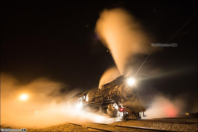 2015年2月23日。哈密三道岭露天煤矿。夜色下吞云吐雾的建设型蒸汽机车。(图/李刚)