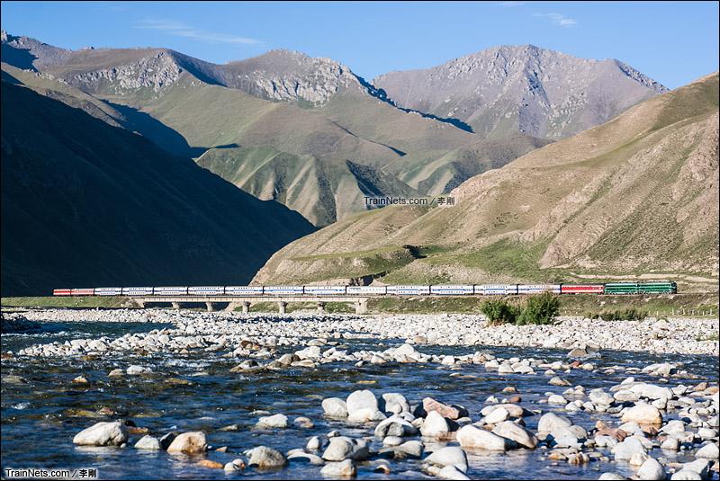 2012年8月13日。南疆铁路。双机DF4B牵引客车K9788次运行在乌拉斯台河河谷中。(图/李刚)