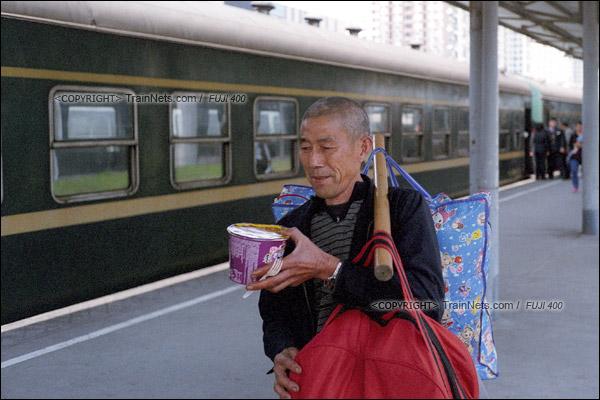 2016年1月9日。下午,深圳西站。最后一班1204次列车开始上客。一位返乡的民工扛着行李,提着泡面准备上车。(F5929)
