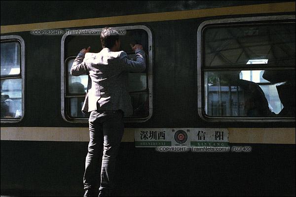 2016年1月9日。下午,深圳西站。最后一班1204次列车开始上客。一位送孩子的市民把头探到窗边,为孩子安排座位。(F6013)