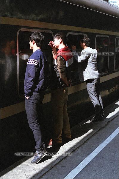 2016年1月9日。下午,深圳西站。最后一班1204次列车开始上客。三位送亲人的市民齐齐站在窗边对着车里说话。(F6016)