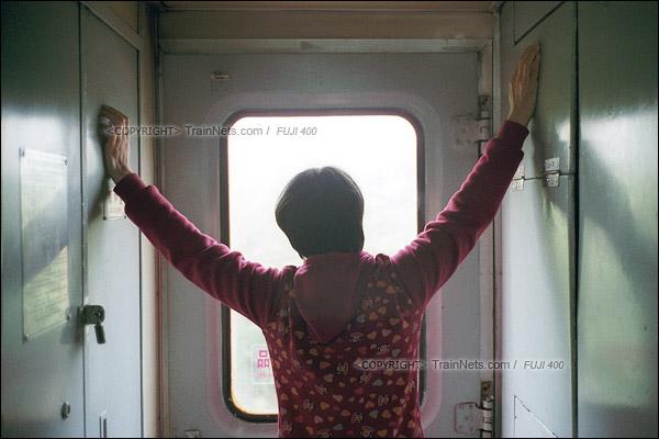 2016年1月9日。一位无座的乘客在车门前伸展着全身,看着窗外的风景。(F6126)