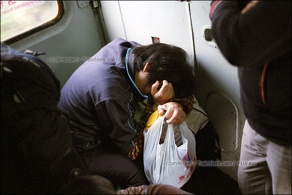 2016年1月9日。一位无座乘客窝在车门处睡觉。(F6203)