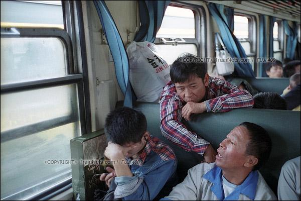 2016年1月9日。两名从东莞东站上车的工友专心地聊着天。这节绿皮车使用的是上开窗式窗户,冬天运行时通风降温,寒风也不会直吹乘客。(F6207)