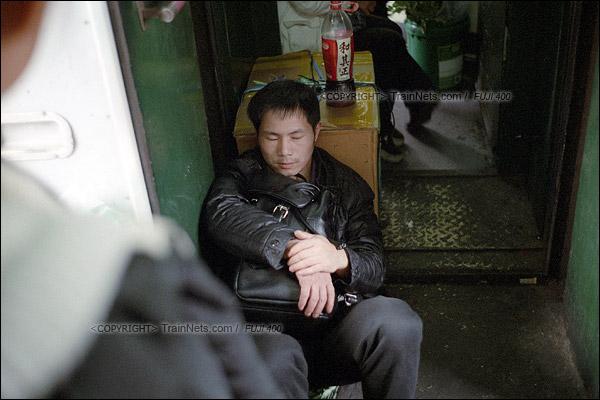 2016年1月9日。一位无座乘客直接躺在自己的行李上休息。(F6208)