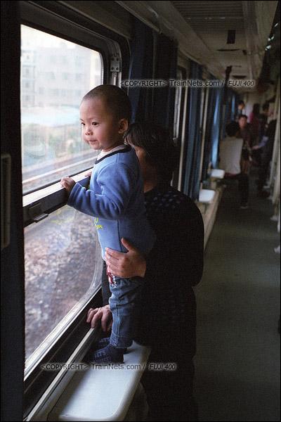 2016年1月9日。列车即将抵达龙川站,一名孩子好奇地看着窗外的景物。(F6227)