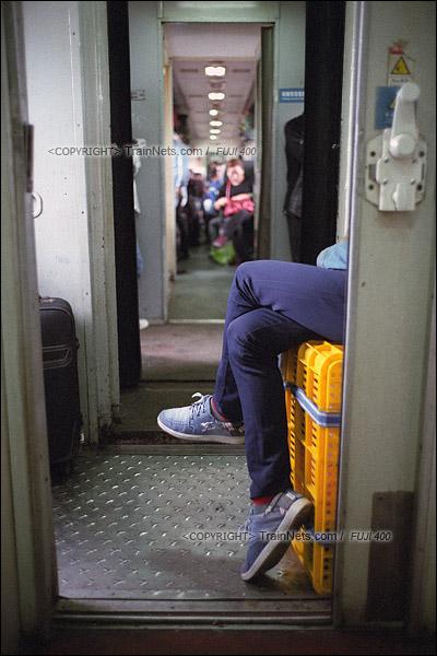 2016年1月9日。一位无座乘客,潇洒地坐在自己的行李箱上玩着手机。(F6234)