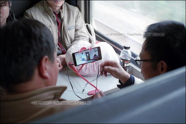 2016年1月9日。过去乘火车是与邻座聊天,如今科技发达了,两名乘客自带支架看着电视剧。(F6313)