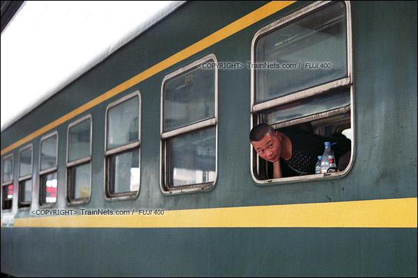 2016年1月9日。1204次列车停靠龙川站,一位乘客探头观看站台的人群。(F6322)