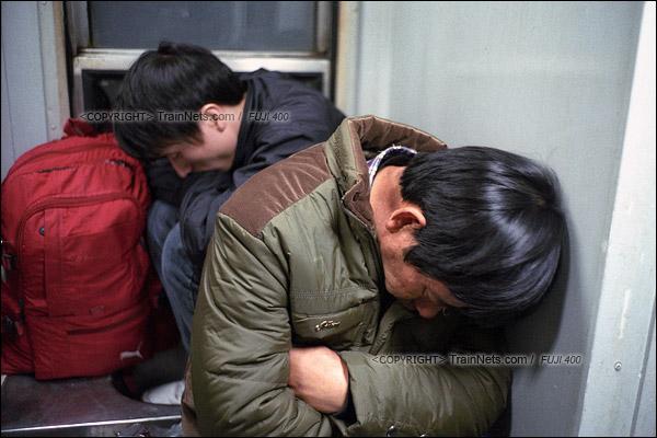 2016年1月10日。凌晨四点,寒风从窗缝中涌入,两名无座乘客蜷缩在洗手台的位置睡觉。(F6406)