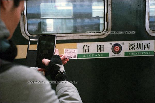2016年1月10日。1204次列车抵达河南信阳站。一位火车迷拿这车票与水牌留影。(F6504)