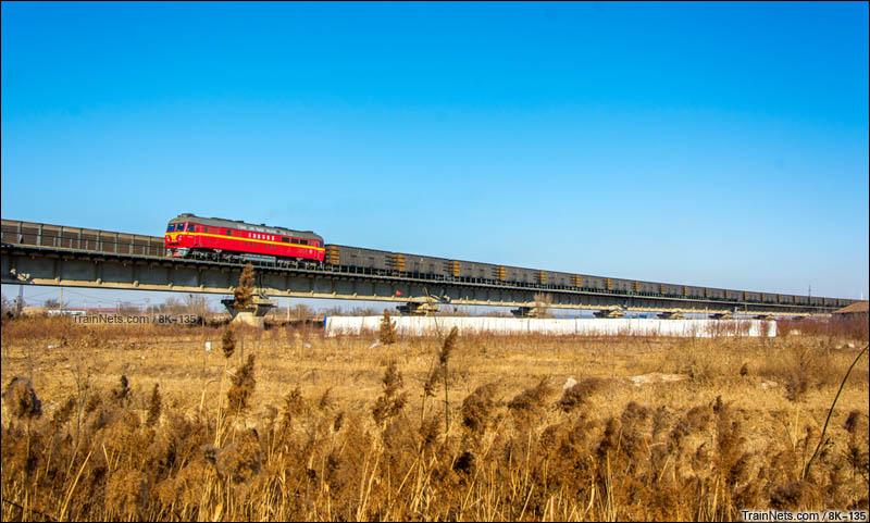 2016年1月7日。天津市大港区。天津南环的DF8B型机车牵引货列下行通过黄万线大桥。(图/8K-135)