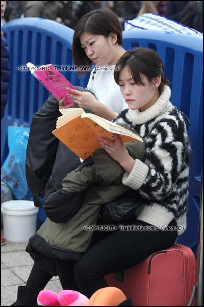 2016年1月29日。下午,广州火车站。由于列车晚点,广场里挤满了等待的旅客。两位女生利用空余时间读书。(IMG-7960-160129)
