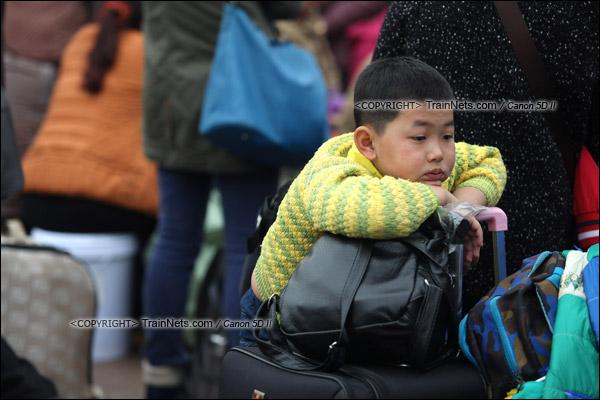 2016年1月29日。下午,广州火车站。由于列车晚点,广场里挤满了等待的旅客。一名孩子无奈地坐在行李上等待。(IMG-7967-160129)