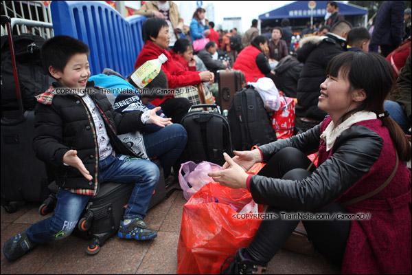 2016年1月29日。下午,广州火车站。由于列车晚点,广场里挤满了等待的旅客。一名孩子和母亲玩着抛瓶子的游戏解闷。(IMG-8003-160129)