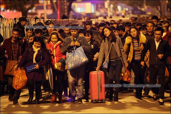 2016年2月1日。晚上9点半,广州火车站。环市路被作为旅客安置点,警方在此设置关卡,分批放行排队进站的旅客。阻隔放开后,乘客纷纷向前小跑。(IMG-8653-160201)