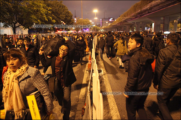 2016年2月1日。晚上9点半,广州火车站。环市路被作为旅客安置点,警方在此设置关卡,分批放行排队进站的旅客。栏杆左侧与右侧的时间差约为两小时。(IMG-8744-160201)