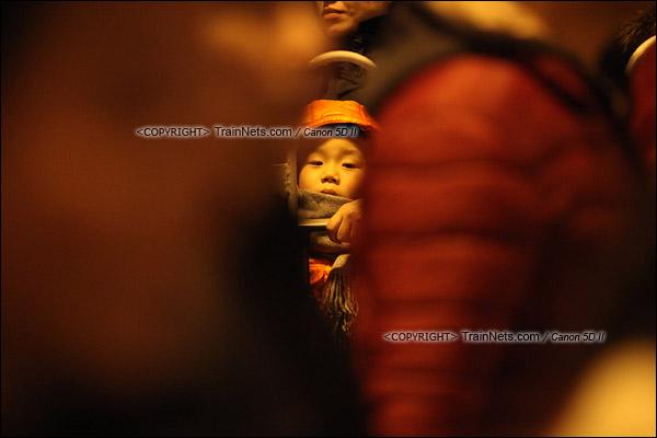 2016年2月1日。晚上9点半,广州火车站。环市路被作为旅客安置点,警方在此设置关卡,分批放行排队进站的旅客。在人群中等待的孩子。(IMG-8874-160201)