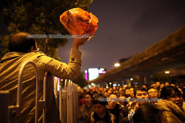 2016年2月1日。晚上9点半,广州火车站。环市路被作为旅客安置点,警方在此设置关卡,分批放行排队进站的旅客。一名已经进站的乘客高举物品,寻找未联络上的同伴。(IMG-8899-160201)