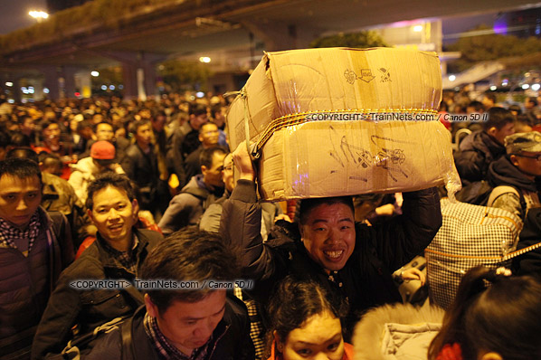 2016年2月1日。晚上9点半,广州火车站。环市路被作为旅客安置点,警方在此设置关卡,分批放行排队进站的旅客。一位乘客头举行李,慢慢前行。(IMG-8917-160201)