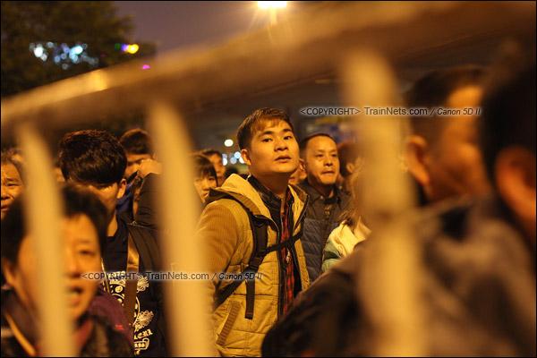 2016年2月1日。晚上9点半,广州火车站。环市路被作为旅客安置点,警方在此设置关卡,分批放行排队进站的旅客。正在等待放行的旅客心急如焚。(IMG-9032-160201)