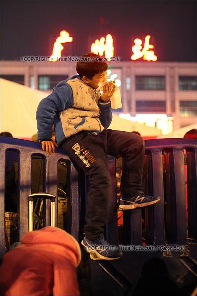 2016年2月1日。晚上10点,广州火车站广场。一名孩子坐在水马上吃着宵夜。(IMG-9168-160201)